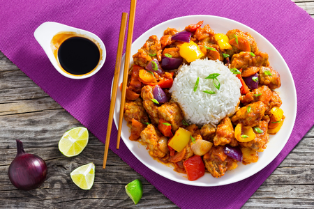 rice with Sweet and Sour fried pork chunks with bell peppers, onion and pineapple on white dish with chopsticks, on old wooden table with soy sauce and slices of lime, close-up