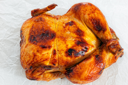 whole chicken: delicious whole chicken roasted in oven on parchment paper, close-up, view from above
