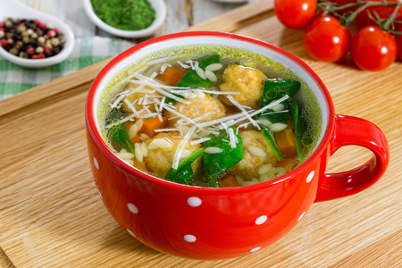 delicious italian wedding chicken soup with meatballs, small pasta risoni,spinach and vegetables in red cup on chopping board, view from above, close-up Archivio Fotografico