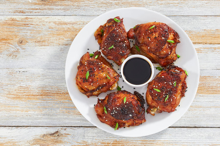 delicious grilled chicken thigh on white plate sprinkled with black, white sesame seeds, and green onion, soy sauce in center of dish, view from above
