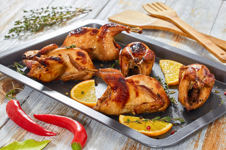 quail: grilled whole quails with thyme and garlic in roasting dish on dark background with chili pepper, bay leaf and wooden spatulas, close-up