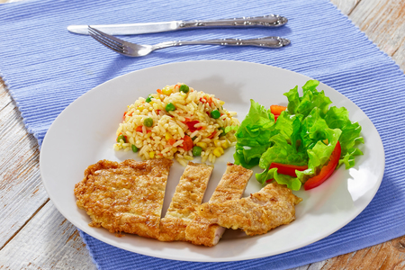 Southern Fried Pork Chops cut in pieces  with risotto and fresh lettuce and bell pepper salad on white plate on table mat with fork and knife, close-up