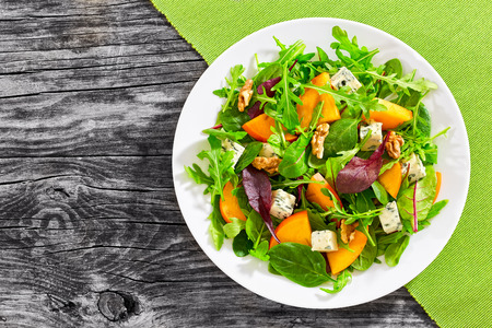 healthy delicious winter salad with persimmon slices, mix of spinach, arugula and lettuce leaves with blue cheese and walnuts on white plate on old dark wooden boards, view from above