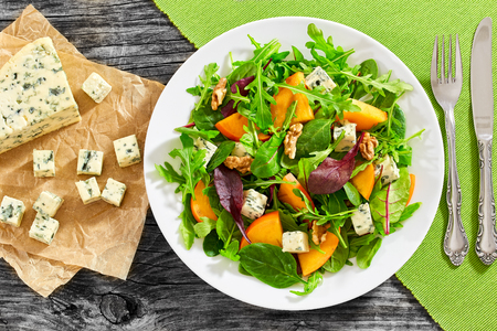 healthy delicious salad with persimmon slices, mix of lettuce leaves, blue cheese cut in cubes and walnuts on white plate. Pieces cheese with mold on paper on dark wooden boards, view from above