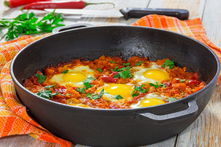 delicious middle east  shakshuka - fried eggs, onion, bell pepper, tomatoes, chilli and spices in cast iron stewpan with kitchen towel on old wooden background, classic recipe, close-up Standard-Bild