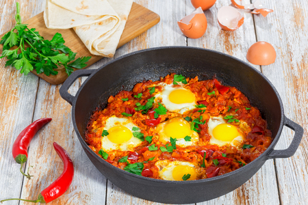 delicious middle east basic shakshuka - fried eggs, onion, bell pepper, tomatoes, chilli and spices in cast iron pan on old wooden background with shells, pita and parsley, close-up, top view 写真素材