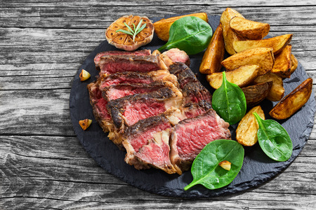 Juicy rib eye beef steak medium rare  with spices cut in slices on slate plate with fried garlic and spinach salad. and fried potato wedges. dark style, view from above Stock Photo