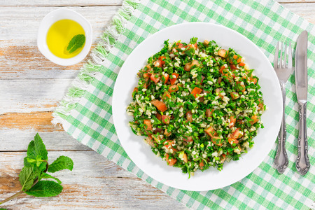parsley salad or Tabbouleh,  Middle Eastern vegetarian dish with bulgur, tomatoes, parsley, spring onion and mint, sprinkled with olive oil and lemon juice, easy and healthy recipe, view from above
