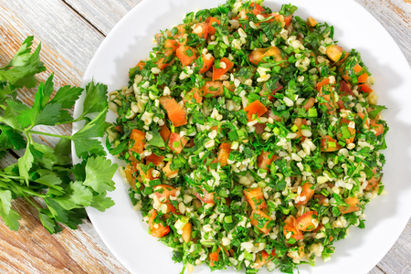 bulgur wheat gluten free vegetarian parsley,mint, spring onion, tomato salad, drizzled with lemon juice and olive oil on white dish on peeling paint table, authentic recipe,close-up, view from above Foto de archivo