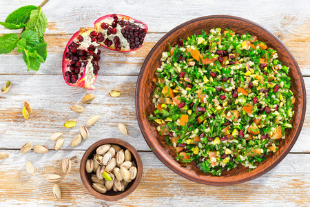 delicious tabbouleh salad with pomegranate, pistachio nuts, parsley, peppermint, spring onion, tomato, drizzled with lemon juice and olive oil, close-up, view from above