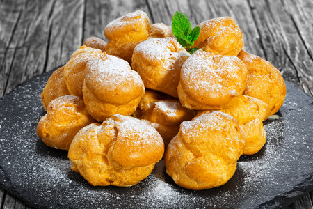 Delicious profiteroles filled with cream on slate plate,  dusting of powdered sugar and decorated with mint, on old dark wooden table, close-up Stock Photo