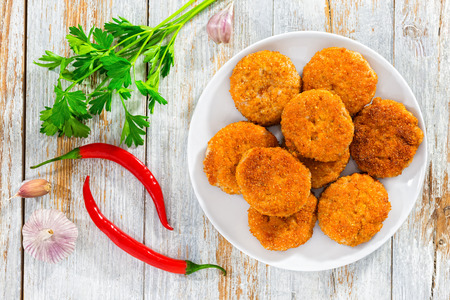 Juicy delicious breaded meat cutlets on white plate on wooden table with parsley, garlic and red chili peppers on background, view from above