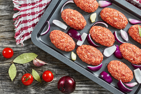 fresh ground raw meat cutlets in baking dish with red onion, garlic and bay leaves drizzled with olive oil to prepare for frying in oven, view from above, close-up Stock Photo