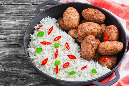 rice and juicy delicious meat cutlets  sprinkled with chili pieces and green herbs in iron stew pan on kitchen towel. chili peppers on old rustic boards, view from above, close-up Stock Photo