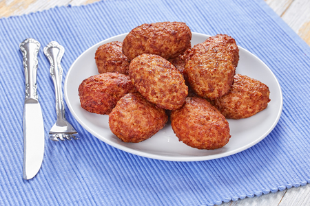 juicy delicious fried meat cutlets on white platter on kitchen table mat, view from above, close-up Stock Photo