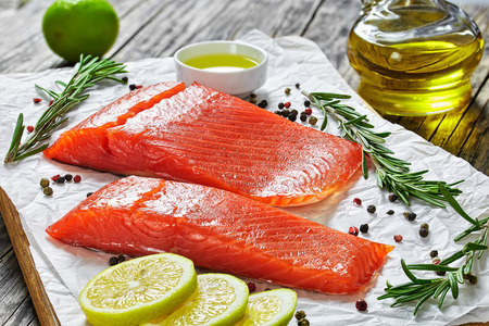 two pieces of salted salmon fish fillet with fresh rosemary, mix of pepper, oil in gravy boat on chopping board on paper, close-up Archivio Fotografico