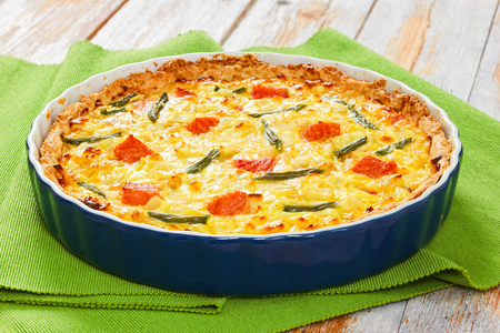 Salmon and green bean quiche tart with Emmental cheese, cream, onion and eggs in baking dish on green table mat on old wooden table, close-up, view from above