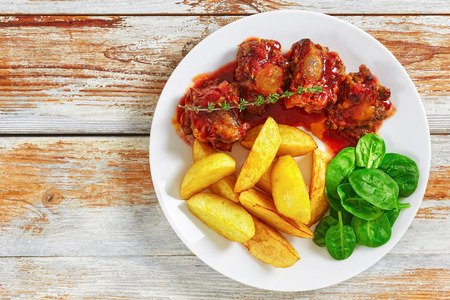 rabo de toro or oxtail stew in red wine tomato sauce on white plate with spinach salad and fried potato wedges, authentic recipe, view from above, close-up