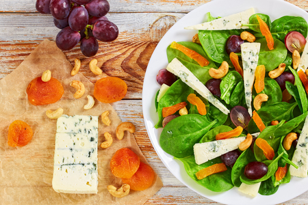 fresh grape, blue cheese, spinach, dried apricots and cashew healthy salad on white platter on old white wooden table, view from above, close-up Stock Photo