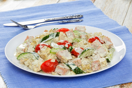 delicious salad with meat, cucumber, tomato, cheese, omelette cut in strips and apple slices with yogurt mustard dressing on white plate with cutlery on background, view from above, close-up