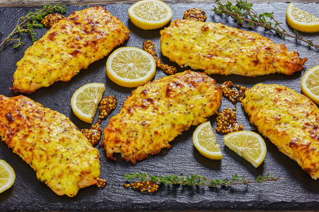delicious Baked Chicken breast with emmental cheese and Whole-grain mustard on black slate with thyme and lemon slices, close-up, top view Archivio Fotografico