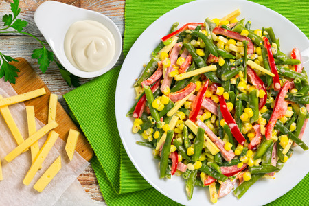 green beans, sweet corn kernels, red bell pepper, ham and cheese  nutrient-rich succotash salad on white platter with ingredients and homemade dressing on background, view from above, close-up Stock Photo