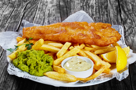 delicious crispy fish and chips - fried cod, french fries, lemon slices, tartar sauce and mushy peas on plate on paper, on wooden table, front view from above, close-up