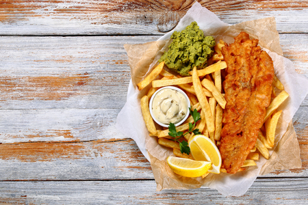 delicious crispy fish and chips - fried cod, french fries, lemon slices, tartar sauce and mashed peas on plate on paper on old wooden tabletop, authentic british recipe, view from above, blank space left