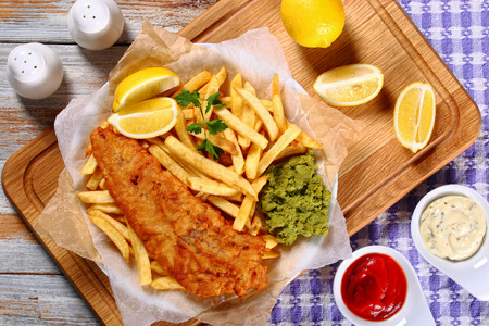 crispy fish and chips - fried cod, french fries, lemon slices, tartar sauce and mashed peas on plate on paper on old wooden table with rosemary in mortar, authentic recipe, view from above Stock Photo