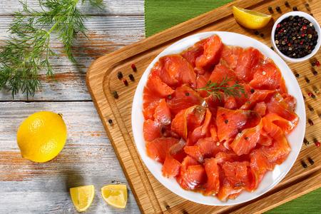 ディルの白い平板のおいしい赤魚の切り身と、まな板の上の唐辛子のスライスを上から表示します。木製のテーブルに新鮮なディルとレモン