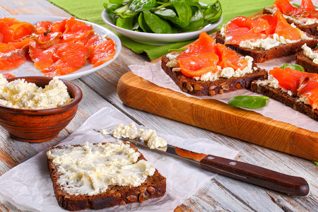 delicious rye bread toasts smothered with cream cheese and topped with salmon slices on white paper on cutting board. bowl of fresh spinach  salad and ingredients on background, view from above