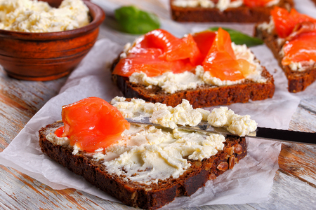 rye bread toasts smothered with cream cheese and topped with salmon slices, knife and bowl with cheese on white paper with spinach leaves, view from above, close-up, macro