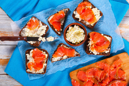 delicious rye bread toasts smothered with cream cheese and topped with salmon slices on white paper. knife and cutting board with salmon fillet on old wooden table, view from above, close-up Stock Photo