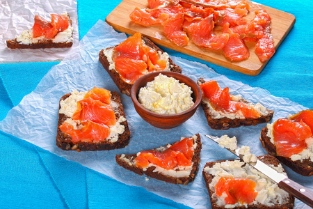 rye bread toasts smothered with cream cheese and topped with salmon slices, knife and bowl with cheese on white paper. cutting board with salmon fillet on background, view from above, close-up