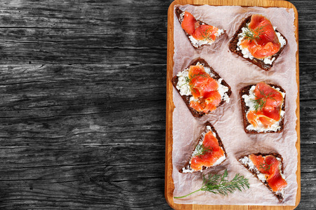 delicious toast with cream cheese and salmon on whole grain rye bread with sunflower seeds on chopping board on dark wooden table, view from above Stock Photo