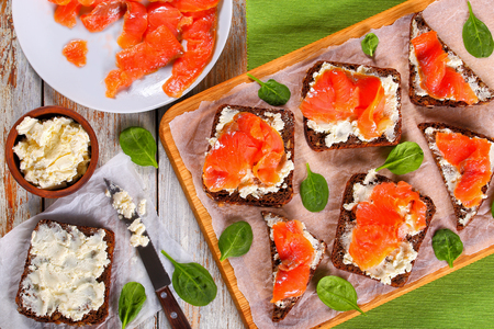 delicious rye bread toasts smothered with cream cheese and topped with salmon slices on white paper on cutting board. ingredients on background, view from above