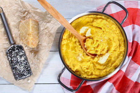 delicious hot polenta porridge with butter and grated cheese in pan with wooden spoon,  grater with piece of parmesan cheese on paper on white table, authentic italian recipe, view from above