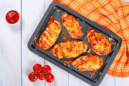 delicious grilled in oven Chicken breasts layered with melted emmental cheese, vegetables and tomato sauce on non-stick baking sheet on white table with kitchen towel, view from above
