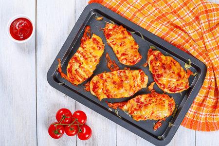 オーブン鶏の胸肉と溶けたエメンタール チーズ層においしい焼き、上からの眺めノンスティック天板キッチン タオルの白いテーブルの上に野菜とトマトのソース 写真素材 - 75710315