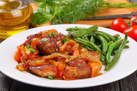 delicious meat stew with vegetables and spices served with crispy fried green bean chips on plate on old dark wooden table. greens, olive oil and tomatoes on background, view from above, close-up