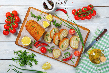 delicious baked in oven Gefilte fish loaf cut in slices on chopping board with scallions, parsley, lemon, chili peppers. olive oil, pepper mix and fresh tomatoes on white worktop,  view from above