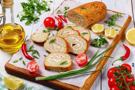 close-up of delicious baked in oven Gefilte minced white fish fillets roll-up with crab meat cut in slices on chopping board with scallions, fresh spring parsley, lemon, chili peppers, view from above Stock Photo