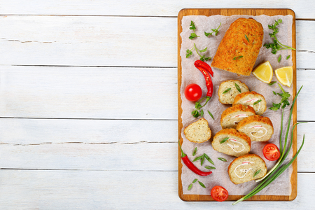 delicious baked in oven Gefilte minced white fish fillets roll-up with crab meat cut in slices on chopping board with scallions, fresh spring parsley, lemon, chili peppers, top view, blank space lef Stock Photo