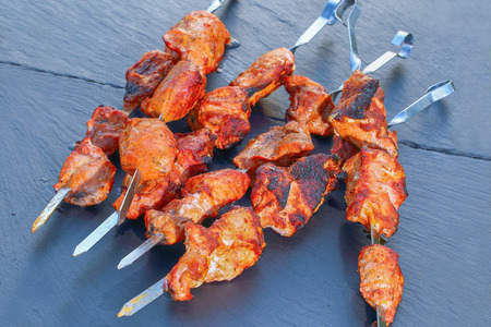 delicious juicy chargrilled meat fillet on metal skewers on black slate trays, view from above, close-up Stock Photo