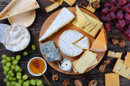 cheeseboard: set of authentic french Cheese plate served with grapes, honey, homemade chocolate sweets and nuts on wooden round tray on dark wooden background, view from above