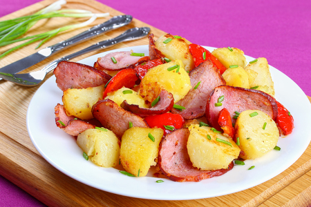 Potato fried in butter with ham and red bell pepper chunk, sprinkled with spring onion on white plate. fork, knife and green onion on background, close-up Stock Photo
