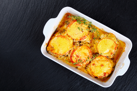 delicious flavour meat chops layered with fried mushrooms, onion, tomato and covered with melted cheese in gratin dish on black stone slate tray, view from above