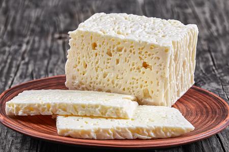 正確 - フェタチーズ羊やヤギのミルク、木製のテーブル、上からの眺め、クローズ アップの粘土板のスライスにカットから白いギリシャのチーズ豆