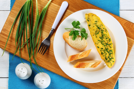 delicious basic French tender omelette served on white plate with baguette slices and fresh parsley on cutting board with salt and pepper shakers and spring green onion, view from above