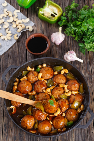 Chicken or turkey meatballs smothered in sauce of green bell pepper, onion, soy sauce, chinese cooking wine and spices in pan, ingredients on wooden background close-up, vertical view from above Stock Photo